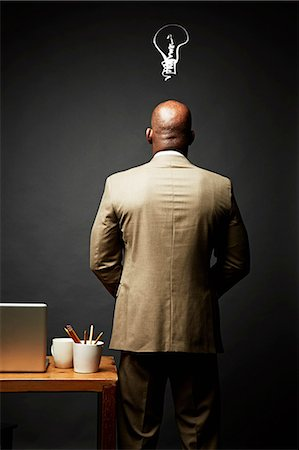 Back view of man thinking of idea Stock Photo - Premium Royalty-Free, Code: 614-06898197
