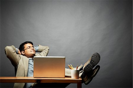 Man relaxing with feet up on table Stock Photo - Premium Royalty-Free, Code: 614-06898223