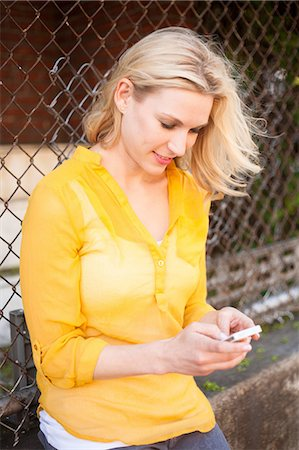 Woman using mobile phone against chain link fence Stock Photo - Premium Royalty-Free, Code: 614-06898261