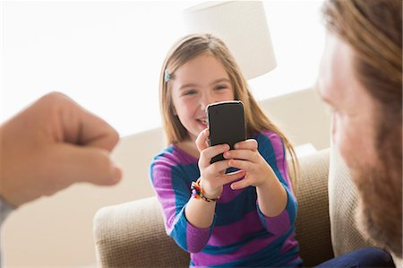 Daughter photographing father with smartphone Stock Photo - Premium Royalty-Free, Code: 614-06898281