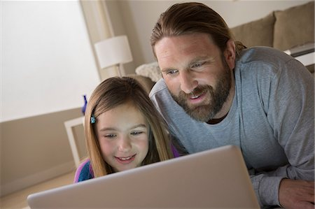 Father and daughter looking at laptop Stock Photo - Premium Royalty-Free, Code: 614-06898283