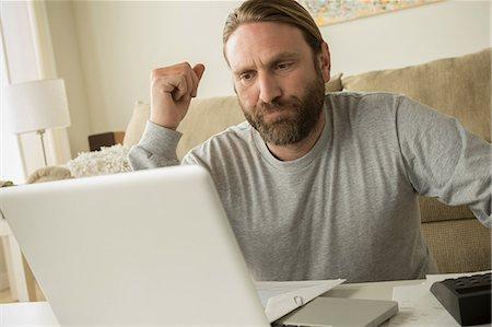 Man looking at laptop Stock Photo - Premium Royalty-Free, Code: 614-06898293