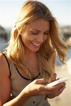 Woman smiling at text message on mobile phone Stock Photo - Premium Royalty-Free, Code: 614-06898347