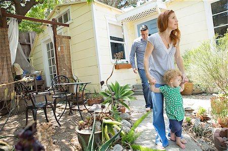 Parents & child walking in the backyard Stock Photo - Premium Royalty-Free, Code: 614-06898408
