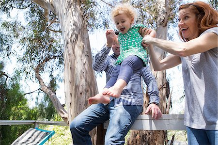 Parents swinging child by the arms Stock Photo - Premium Royalty-Free, Code: 614-06898419