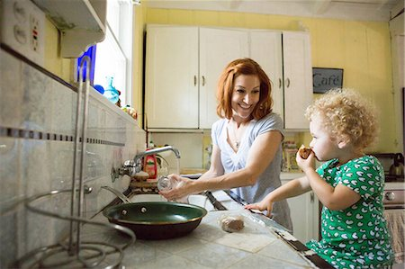 patterned - Mother at sink smiling at child Stock Photo - Premium Royalty-Free, Code: 614-06898428