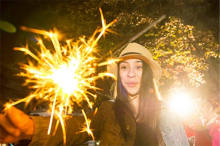 Girl playing with sparkler Stock Photo - Premium Royalty-Free, Code: 614-06898441