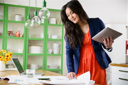 Woman with digital tablet looking through paperwork Stock Photo - Premium Royalty-Free, Code: 614-06898497