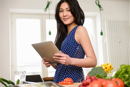 Woman holding digital tablet looking at camera Stock Photo - Premium Royalty-Free, Code: 614-06898506