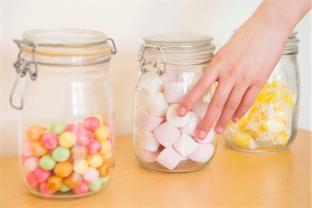 decision - Hand touching jar of marshmallow Stock Photo - Premium Royalty-Free, Code: 614-06898521