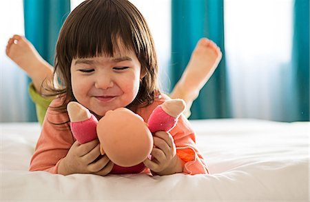 Girl playing with dolly in bedroom Stock Photo - Premium Royalty-Free, Code: 614-06974043