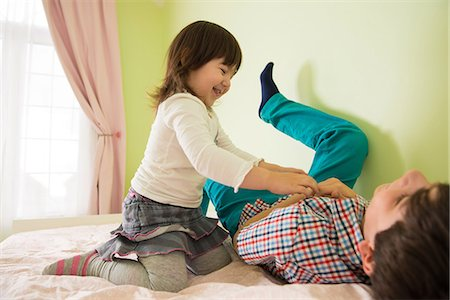 Girl tickling brother on bed Stock Photo - Premium Royalty-Free, Code: 614-06974053