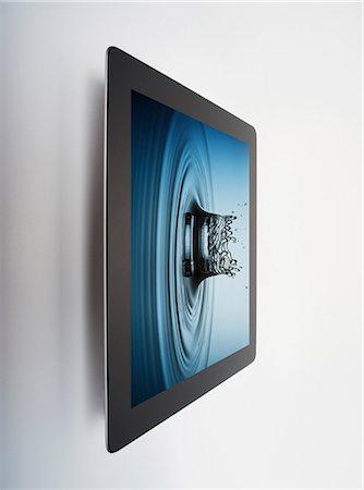 Digital tablet with crown shaped water drop splash on screen Stock Photo - Premium Royalty-Free, Code: 614-06974077
