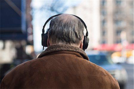 Rear view of senior man wearing headphones Stock Photo - Premium Royalty-Free, Code: 614-06974292