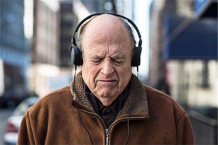 Senior man with eyes closed wearing headphones Stock Photo - Premium Royalty-Free, Code: 614-06974293
