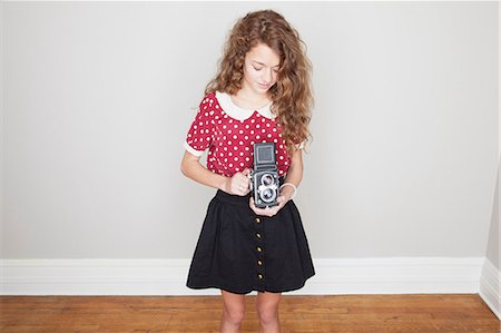 Girl holding old camera Stock Photo - Premium Royalty-Free, Code: 614-06974365