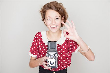 spotted - Girl holding old camera Stock Photo - Premium Royalty-Free, Code: 614-06974366