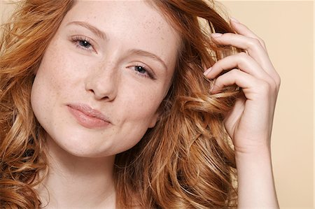 Studio shot of young woman with curly red hair, hand in hair Stock Photo - Premium Royalty-Free, Code: 614-06974526