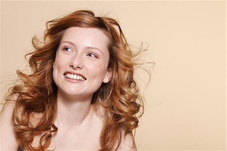 Studio shot of young woman with curly red hair Stock Photo - Premium Royalty-Free, Code: 614-06974528
