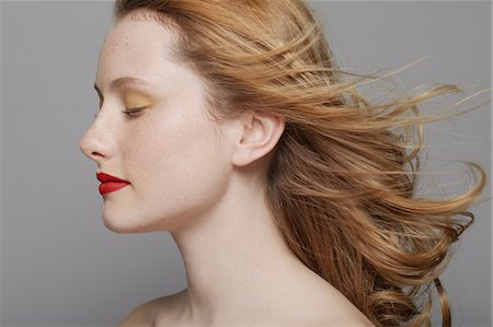 Profile of young woman with curly red hair wearing make up Stock Photo - Premium Royalty-Free, Code: 614-06974538