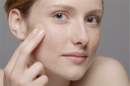 Close up of part of young woman's face, applying concealer Stock Photo - Premium Royalty-Free, Code: 614-06974555