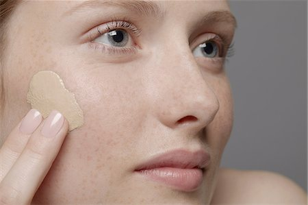 Close up of part of young woman's face, applying concealer Stock Photo - Premium Royalty-Free, Code: 614-06974557