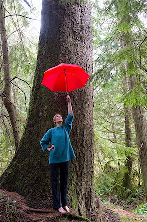 Mature woman holding red umbrella in forest Stock Photo - Premium Royalty-Free, Code: 614-06974593