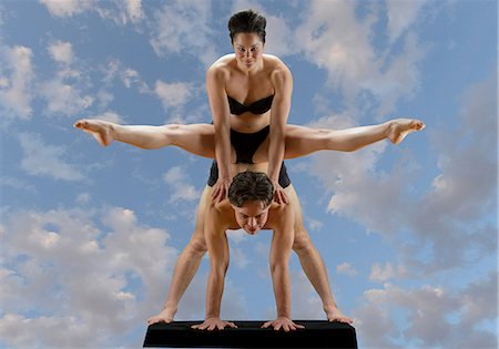 flexible (people or objects with physical bendability) - Mid adult dancers balancing on top of each other against blue sky Stock Photo - Premium Royalty-Free, Code: 614-06974607
