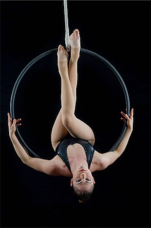 Aerialist performing on hoop in front of black background Stock Photo - Premium Royalty-Free, Code: 614-06974625