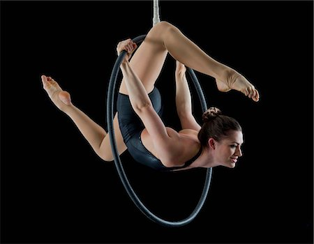 stretch - Aerialist performing on hoop in front of black background Stock Photo - Premium Royalty-Free, Code: 614-06974627