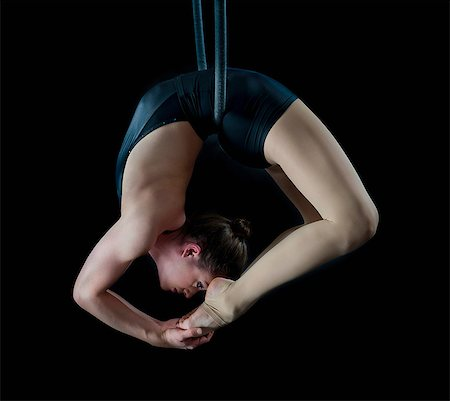 Aerialist performing on hoop in front of black background Stock Photo - Premium Royalty-Free, Code: 614-06974628