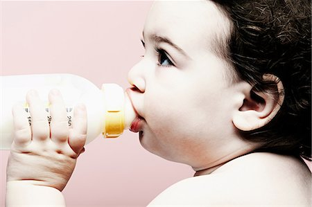 Portrait of baby girl drinking milk from bottle Stock Photo - Premium Royalty-Free, Code: 614-06974697