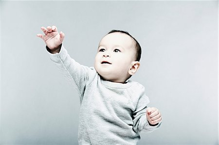 reaching - Portrait of baby boy wearing grey top Stock Photo - Premium Royalty-Free, Code: 614-06974731