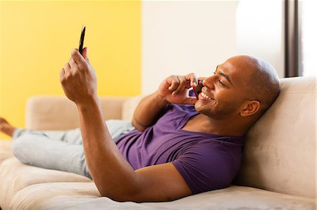 Mid adult male on sofa using digital tablet and mobile phone Stock Photo - Premium Royalty-Free, Code: 614-06974767