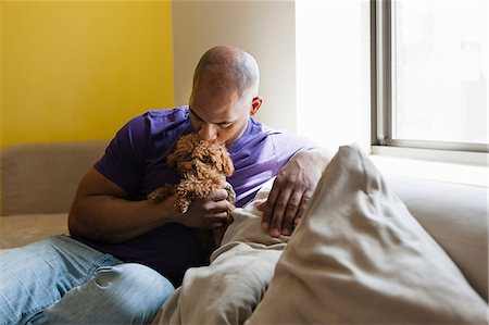 dog kissing man - Mid adult male sitting on sofa with dog Stock Photo - Premium Royalty-Free, Code: 614-06974761