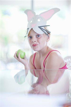 Girl in rabbit costume eating apple Stock Photo - Premium Royalty-Free, Code: 614-06973550