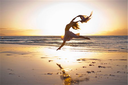 flexible (people or objects with physical bendability) - Young woman dancing on sunlit beach Stock Photo - Premium Royalty-Free, Code: 614-06973611