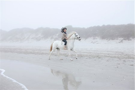 equestrian - Woman riding horse on beach Stock Photo - Premium Royalty-Free, Code: 614-06973728