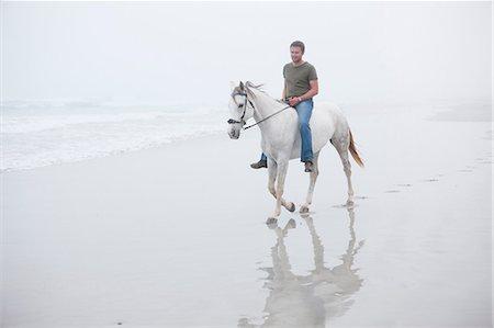 Man riding horse on beach Stock Photo - Premium Royalty-Free, Code: 614-06973734