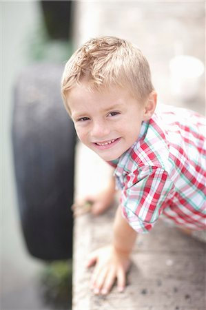 Portrait of young boy leaning on pier wall Stock Photo - Premium Royalty-Free, Code: 614-06973749