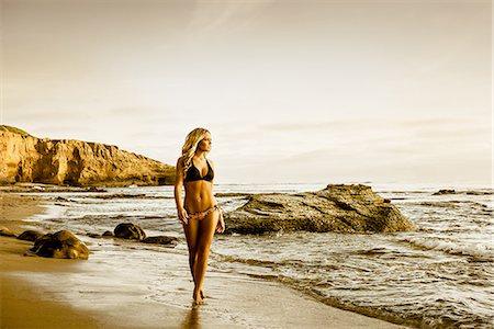 Young woman in bikini walking along beach Stock Photo - Premium Royalty-Free, Code: 614-06973887