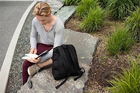 Young man studying text book in park Stock Photo - Premium Royalty-Free, Code: 614-07031096