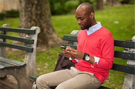 funky - Young man sitting on park bench using mobile phone Stock Photo - Premium Royalty-Free, Code: 614-07031110
