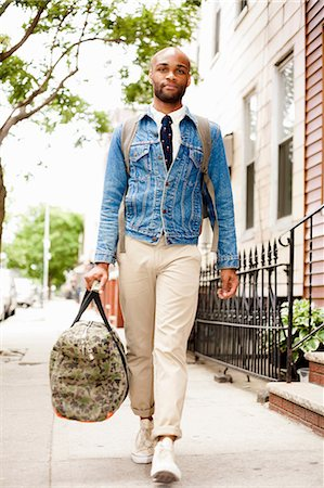 funky - Young man walking down street with holdall Stock Photo - Premium Royalty-Free, Code: 614-07031113