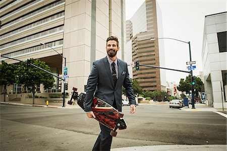Young businessman carrying skateboard and crossing street Stock Photo - Premium Royalty-Free, Code: 614-07031174