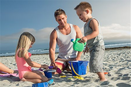 Young man playing with son and daughter on beach Stock Photo - Premium Royalty-Free, Code: 614-07031177