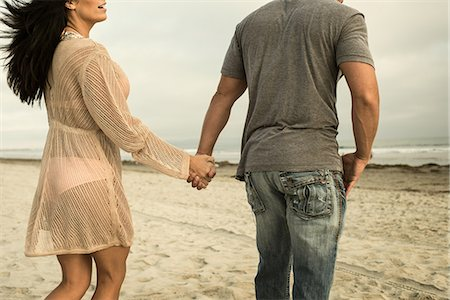 Young couple holding hands on beach Stock Photo - Premium Royalty-Free, Code: 614-07031189