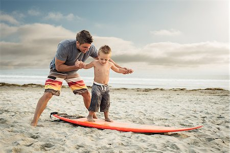 Young man teaching son to surf on beach Stock Photo - Premium Royalty-Free, Code: 614-07031194