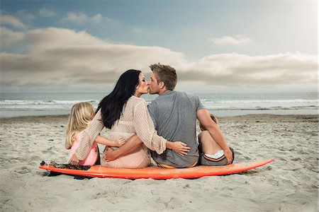 Young family sitting on surfboard on beach with parents kissing Stock Photo - Premium Royalty-Free, Code: 614-07031191