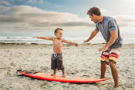 Young man teaching son to surf on beach Stock Photo - Premium Royalty-Free, Code: 614-07031193